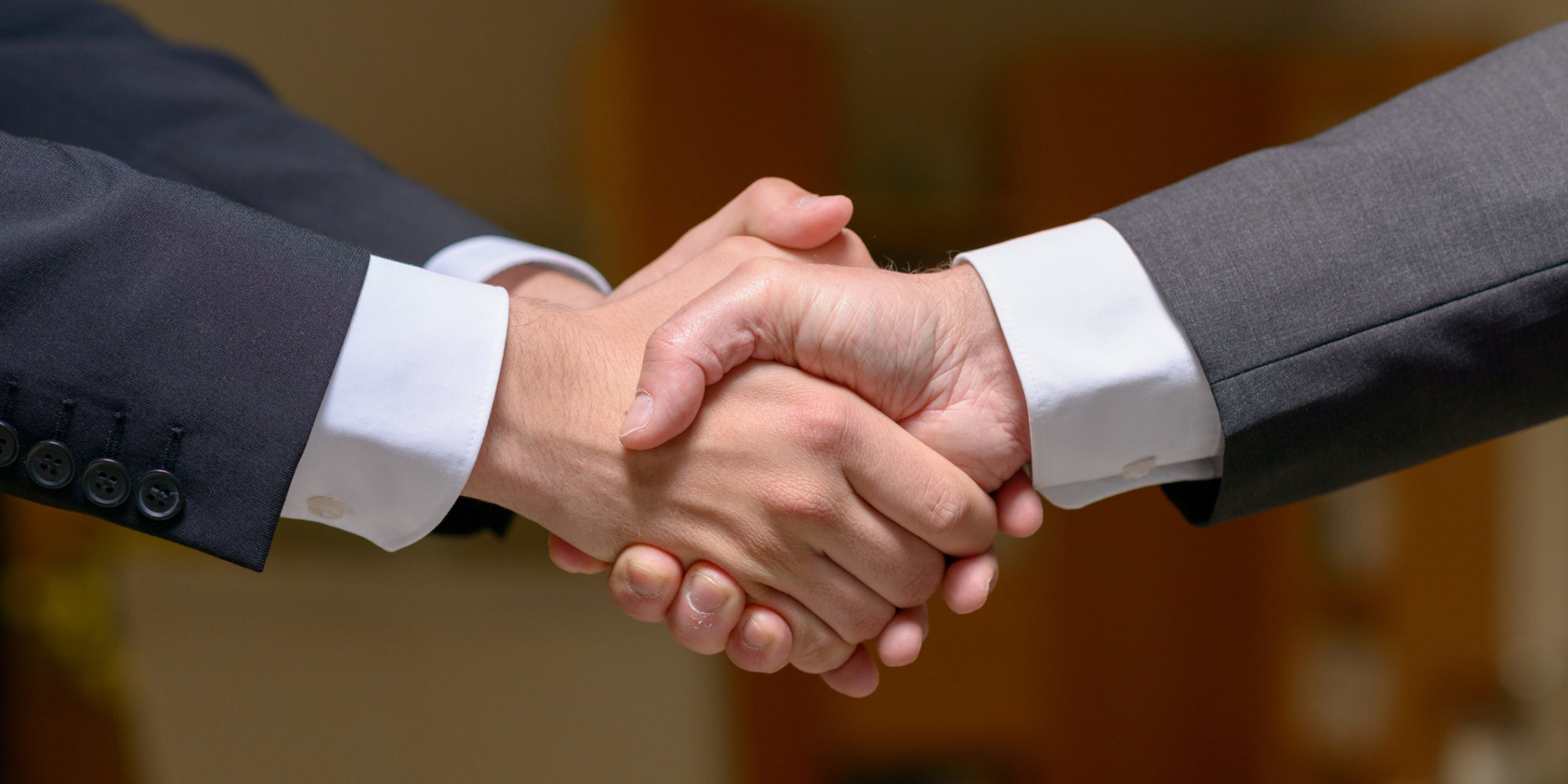 Two businessmen shaking hands outdoors with the enthusiastic younger man clasping the other hand with both hands in a close up view